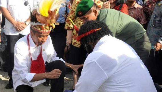 Presiden Joko Widodo (tengah) didampingi Gubernur Papua Lukas Enembe dan Ketua Lembaga Masyarakat Adat Papua (LMA) Lenis Kogoya (kanan) meletakkan batu pertama pembangunan pasar Praha, Sentani, Jayapura, 27 Desember 2014. (Foto: ANTARA)