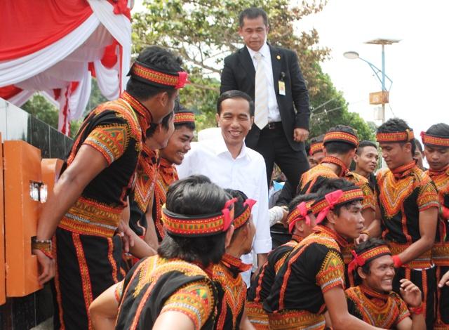 Presiden Jokowi (tengah, baju putih) bersama penari saman berfoto bersama di tugu kilometer nol di Pulau Weh, Sabang, Selasa (10/3/2015)