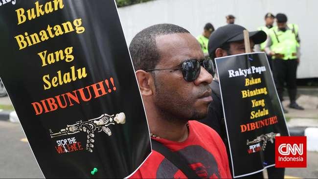 Aktivis dari Koalisi Peduli HAM Papua membawa poster dan spanduk saat unjuk rasa di Jakarta, Senin, 15 Desember 2014. Mereka meminta pemerintah untuk mengusut tuntas kasus kekerasan di Papua yang disinyalir dilakukan oleh Aparat TNI dan Polisi. (CNN Indonesia)