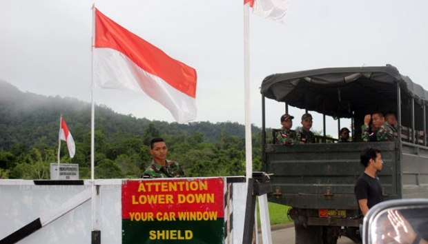 Tentara berjaga dan memeriksa pelintas batas di perbatasan Indonesia - Papua Nugini, 26 Juli 2015. Sebuah alat pemantau baru yang dapat berputar 360 derajat, telah terpasang beberapa minggu sebelum Lebaran. (Foto: TEMPO.CO]