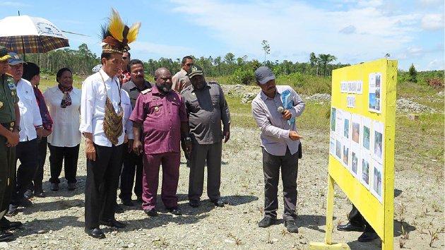 Presiden Joko Widodo menyimak penjelasan pelaksana proyek jalan ruas Nduga-Wamena sepanjang 278 kilometer di Kota Kenyam, Kabupaten Nduga, Provinsi Papua, Kamis (31/12/2015). Presiden menginginkan percepatan pembangunan infrastruktur, terutama jalan di Papua. (KOMPAS)
