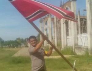 Seorang polisi menurunkan Bendera Bulan Bintang di Aceh Timur (15/08/2016)