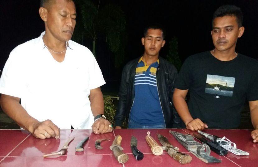 Kapolres Aceh Utara AKBP Untung Sangaji (kiri) beserta barang bukti senjata tajam yang diamankan dalam razia